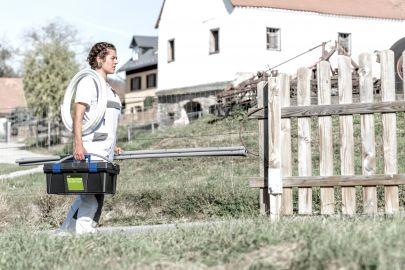 Installateurin geht mit Ausrüstung durch ländlichen Ort.