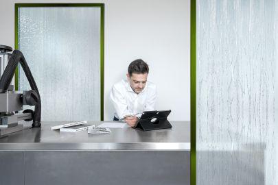 Mann arbeitet an Laptop, dahinter Wasserfall-Kühlung