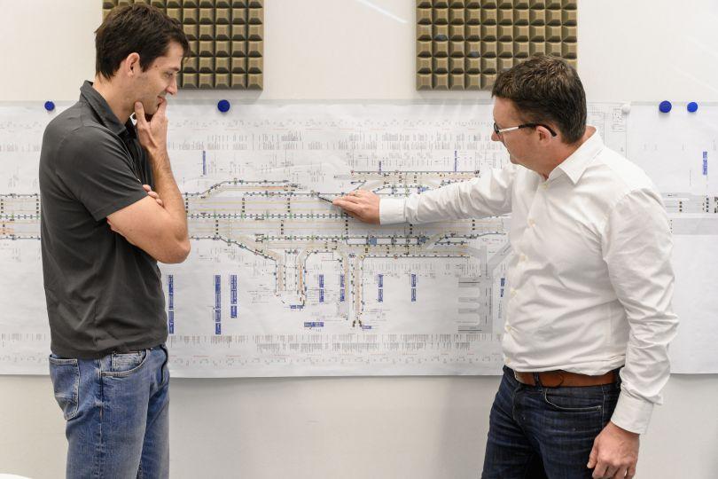 Zwei Männer stehen vor Plan an einer Wand