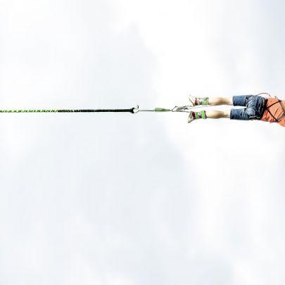 Ein Mann springt an einem Bungee-Seil waagrecht ins Bild.