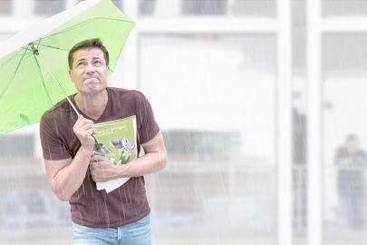 Ein junger Mann hält in einer Hand einen SFG-Folder zum Schutz von geistigem Eigentum, in der anderen einen grünen Schirm, um sich vor dem Regen zu schützen.