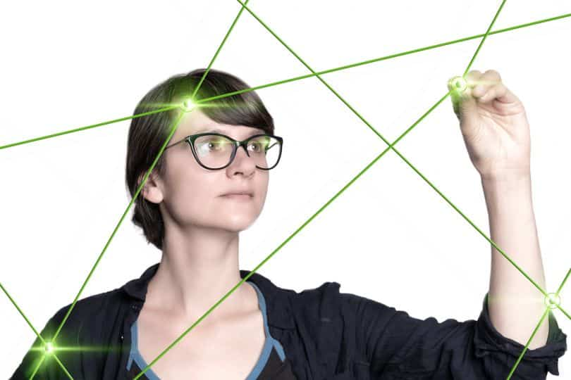 Eine junge Frau malt mit einem Stift Lichtpunkte in ein virtuelles Netz aus grünen Linien.