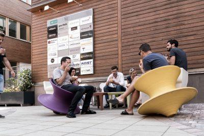 Bürogebäude aus Holz von außen mit Tafel von Firmenlogos. Davor sitzen Personen und essen Eis.