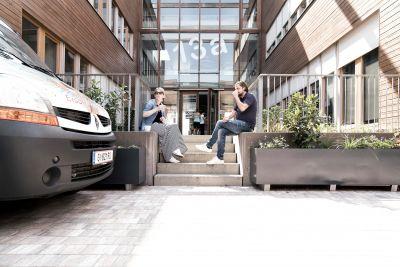 Eingangsbereich von Bürogebäude Außen. Eine Frau und ein Mann sitzen auf Treppe und trinken Kaffee.