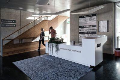 Eingangsbereich von Bürogebäude Innen mit Stiege. Eine Frau und ein Mann durchqueren den Bereich.