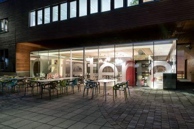Cafeteria aus Glas, beleuchtet von Außen, im Vordergrund Tische und Stühle im Freien