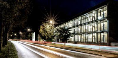 Modernes Gebäude bei Nacht, von Innen beleuchtet, im Vordergrund Straße mit Straßenbeleuchtung