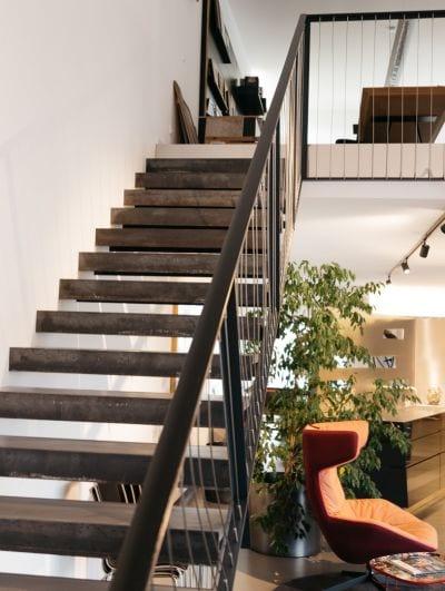 Links offene Stiege nach oben, rechts Lehnstuhl und Zimmerplanze