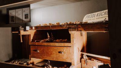 """Alte Werkbank mit Holzspänen, rechts darauf Schild mit der Aufschrift """"Prödl-Küchen"""""""