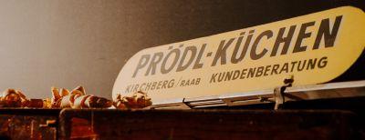 """Schild mit Aufschrift """"Prödl-Küchen"""", links daneben Holzlocken"""