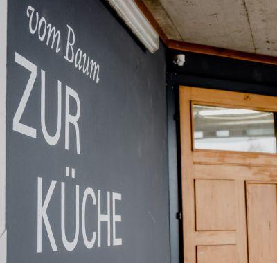 """Links schwarze Wand mit der Aufschrift """"vom Baum ZUR KÜCHE"""", rechts Holztüre"""