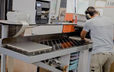 Arbeiter mit Gehörschutz bearbeitet Pressspanplatte