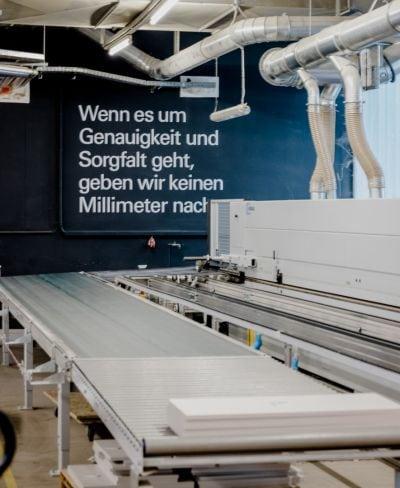 """Sägemaschine und Fließband, hinten Wand mit Aufschrift """" Wenn es um Genauigkeit und Sorgfalt geht, geben wir keinen Milimeter nach."""""""