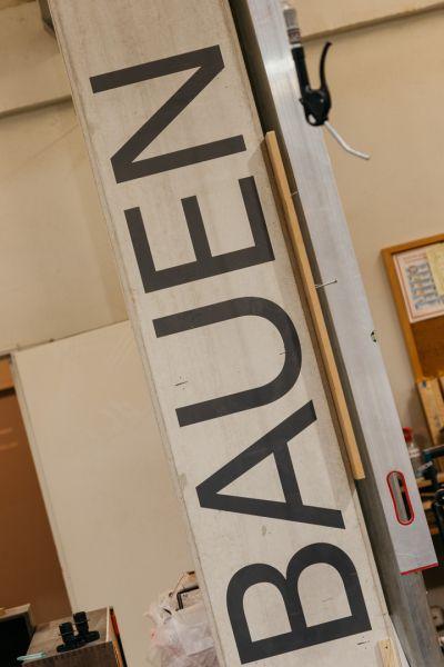 Brett mit schrägem Schriftzug von recht unten nach links oben: BAUEN