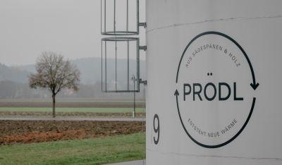 Prödl-Logo im Vordergrund, dahinter Felder und ein kahler Baum