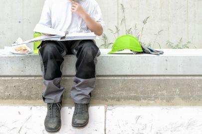 Bauarbeiter, der Pause macht. Den Helm hat er abgelegt - auf seinem Schoß liegt eine Mappe, in der er liest. Im Bild außerdem: Wurstsemmel und Getränkeflasche.