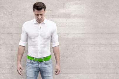 Ein muskulöser Mann trägt Jeans und ein zu kleines, weißes Hemd, das spannt.