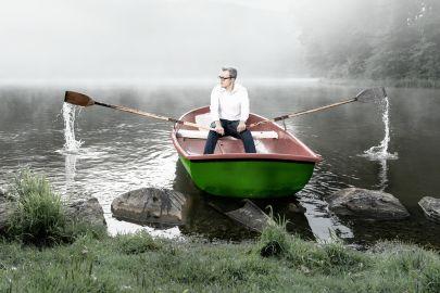 Ein junger Mann in weißem Hemd startet ein grünes Ruderboot in einem nebelverhangenen See