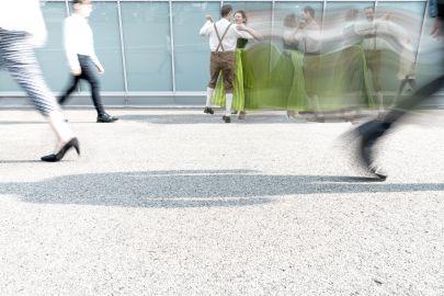 Paar in Tracht tanzt vor moderner urbaner Kulisse.
