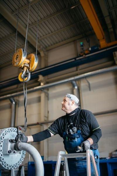 Arbeiter hängt Maschine mit Gurt an Haken