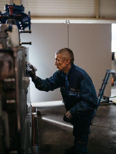 Arbeiter poliert Maschine