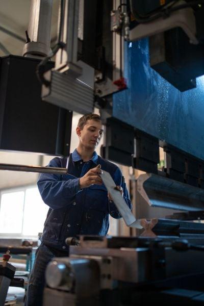 Arbeiter Hält Metallbrett vor Maschine