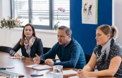 Eine Frau, ein Mann und eine Frau sitzen in Interviewsituation an einem Tisch