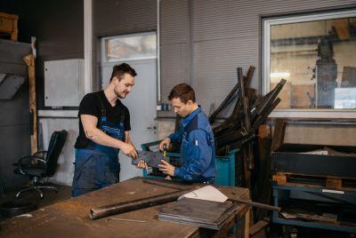 Arbeiter messen gemeinsam ein Metallstück.