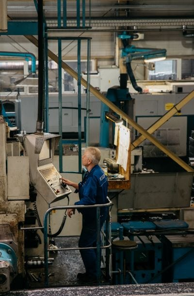 Arbeiter bedient Maschine über Konsole.