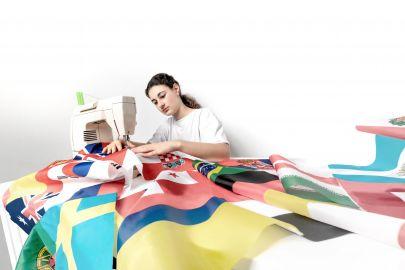 Mädchen näht mit Nähmaschine verschiedene Flaggen zusammen.