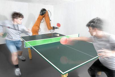 Zwei Jungen spielen einen Tischtennis-Rundgang mit einem Industrieroboter.7