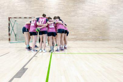 Eine Damen-Handballmannschaft beim Time-out steht in einer Gruppe und steckt die Köpfe zusammen.