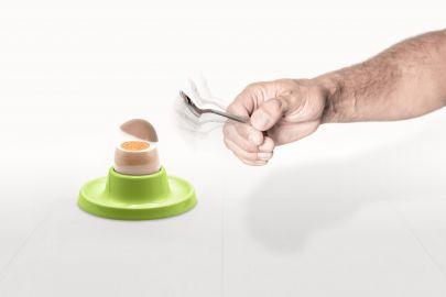 Hand schlägt mit Löffel gekochtes Ei auf. Ei springt mit gerader Bruchstelle auf.