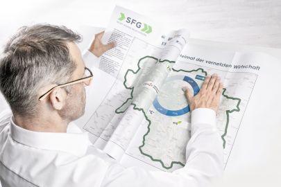 Mann streicht Zeitung mit Steiermark-Landkarte glatt