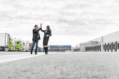 Mann und Frau klatschen vor LKWs ein