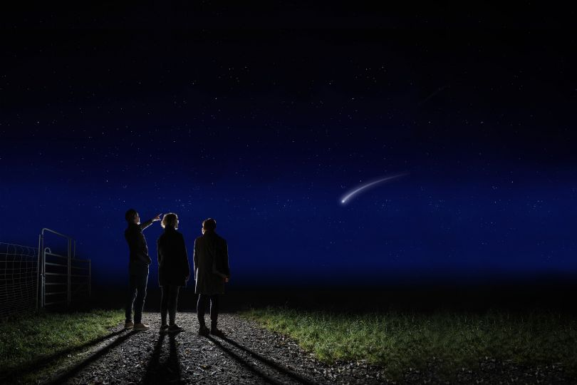 Familie steht in der Nacht auf Weg und beobachtet eine Sternschnuppe