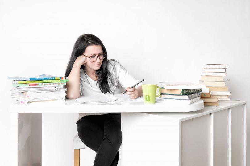 Frau sitzt am Schreibtisch und lernt, vor ihr Bücher und Block