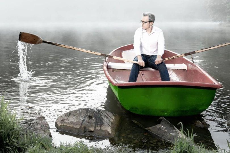 Mann rudert in Boot auf einem See vom Ufer weg