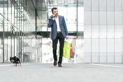 Ein Geschäftsmann spaziert mit einem Hund in der Leine, Einkaustaschen in der Hand telefonierend vor einer Glasfassade.
