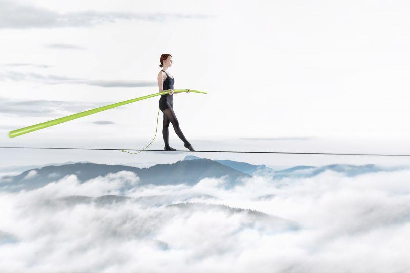 Frau balanciert auf Seil über Berglandschaft mit Wolken, in der Hand hält sie einen grünen Stab.