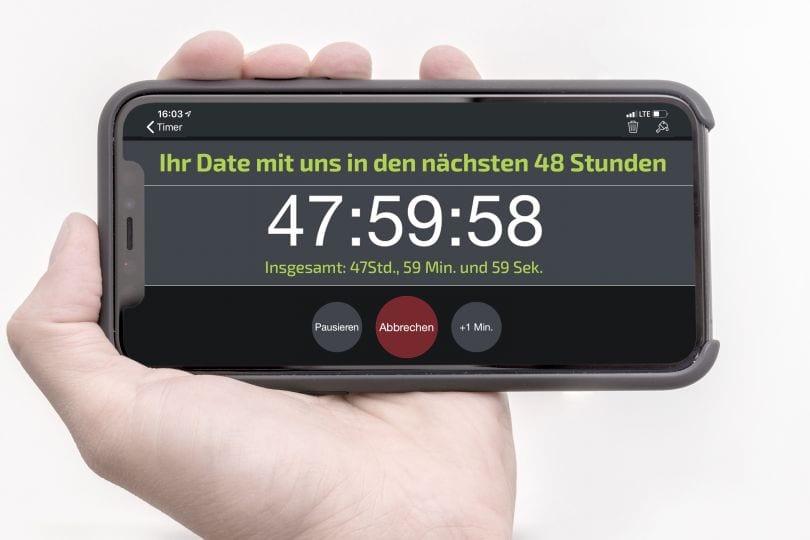 """Hand mit Handy. Auf dem Display steht: """"Ihr Date mit uns in den nächsten 48 Stunden. 47:59:58"""