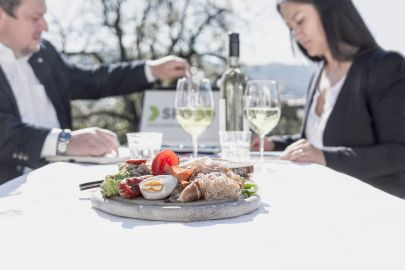 Ein geschäftlich gekleideter Mann und eine geschäftlich gekleidete Frau diskutieren vor einer urigen steirischen Brettljause und steirischem Wein. Im Hintergrund ist eine Mappe mit einem Logo der SFG zu sehen.