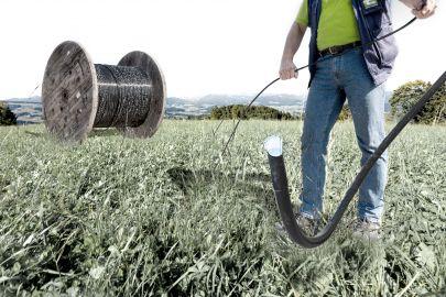 Ein Mann verlegt ein Glasfaser-Kabel auf einer grünen Wiese. Im Hintergrund ist eine riesige Trommel mit Glasfaserkabel zu sehen.
