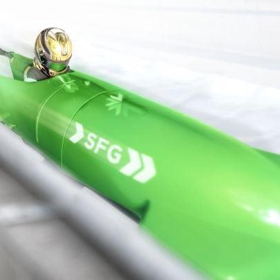 """In einem grünen Bob mit der Aufschrift """"SFG"""" sitzt ein Bobfahrer mit goldenem Helm - ein anderer schiebt ihn von hinten an."""