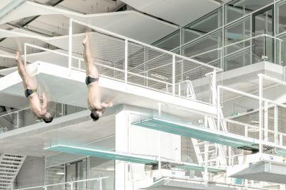 Zwei Männer springen in Hallenbad von 5-Meter-Turm
