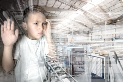 Ein Junge schaut durch eine Glasscheibe auf eine Fabrikshalle.