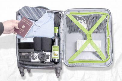 Geöffneter Koffer auf Bett, darin Hemd, Uhr, Socken, Kürbiskernöl, Mehrfachstecker. Hand hält österreichischen Pass darüber.