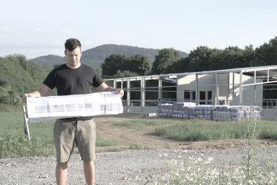 Mann steht mit Plan vor Rohbau