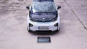 Schwarz-weißer BMW i3 hinter quadratischer, metallischer Ladeplatte