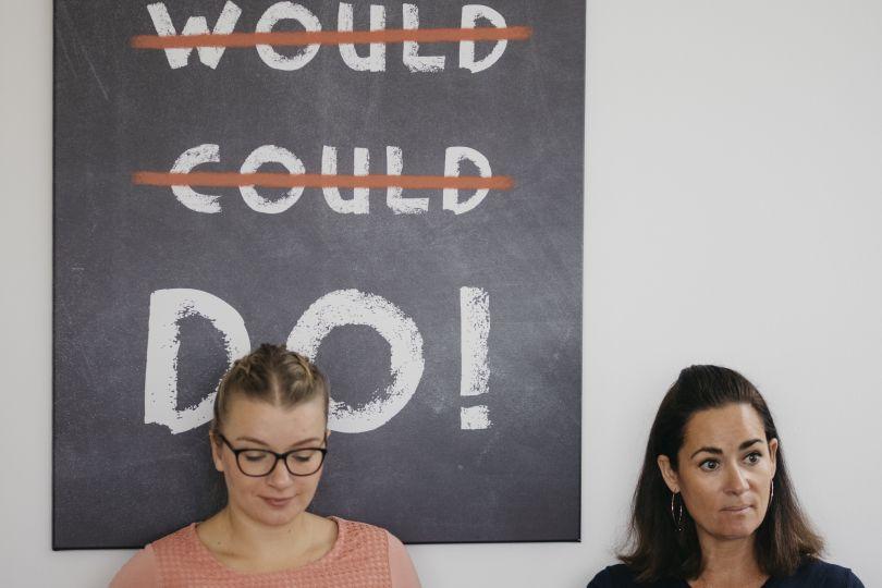 2 Frauen sitzten vor Plakat